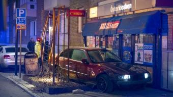 Bil kraschade med parkerade bilar och tobaksaffär