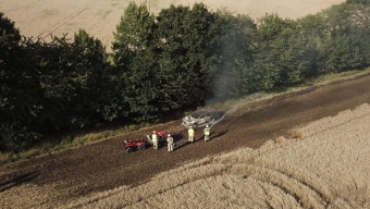 Bil började brinna på åker